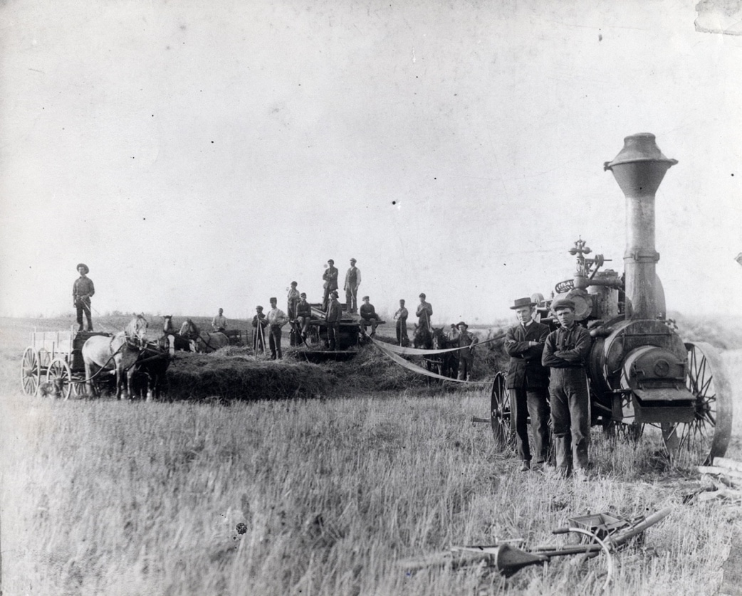 An L.D. Sawyer portable steam engine driving a hand-fed thresher